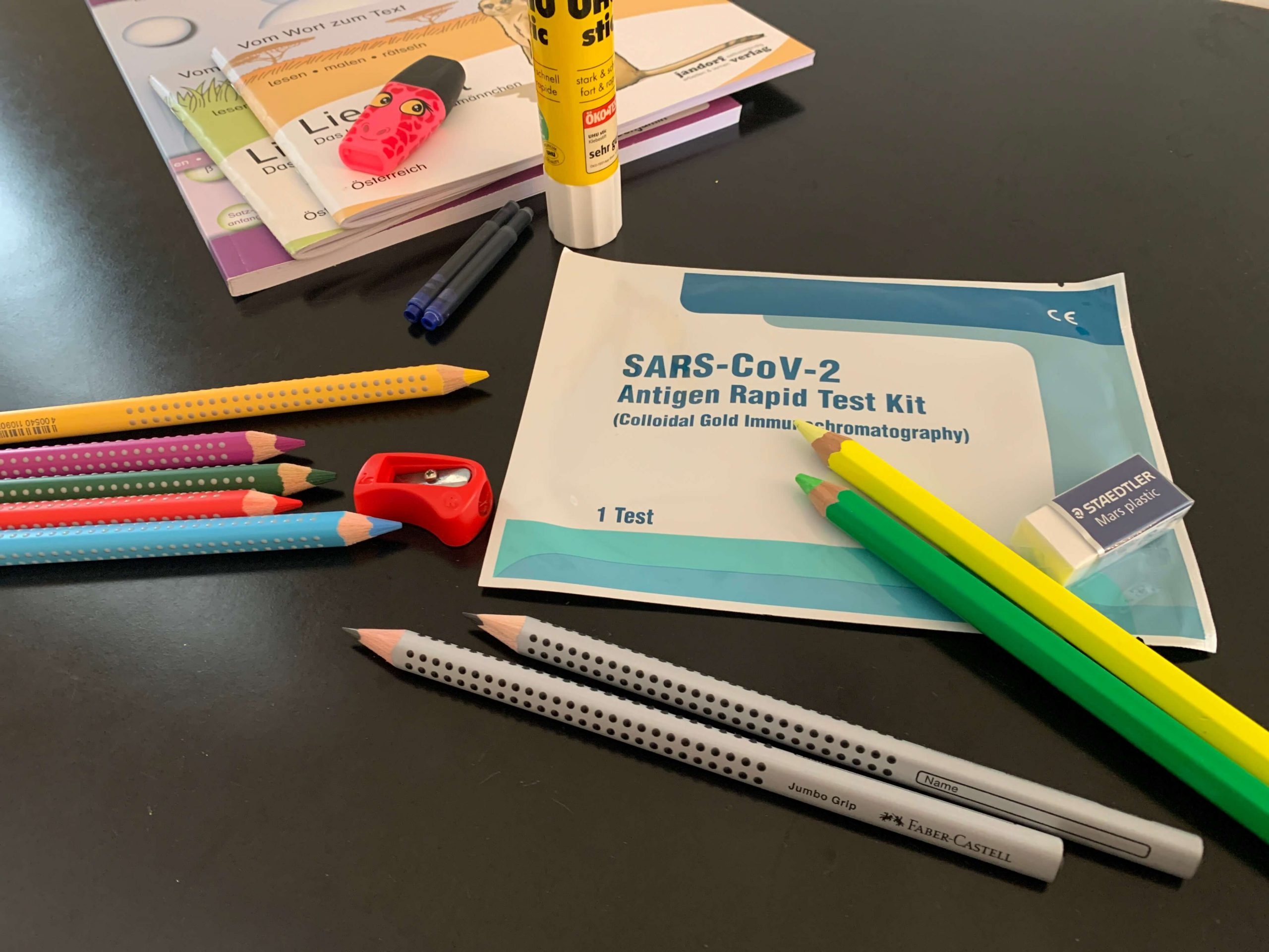 Farbstifte, Schulbücher und Corona-Test